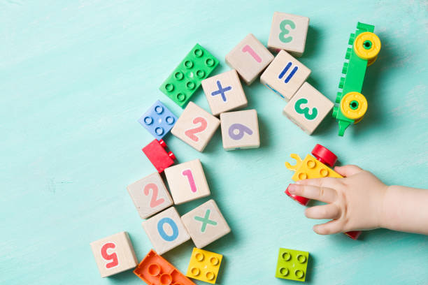 child playing with wooden cubes with numbers and colorful toy bricks on a turquoise wooden background. toddler learning numbers. hand of a child taking toys. - infanzia foto e immagini stock