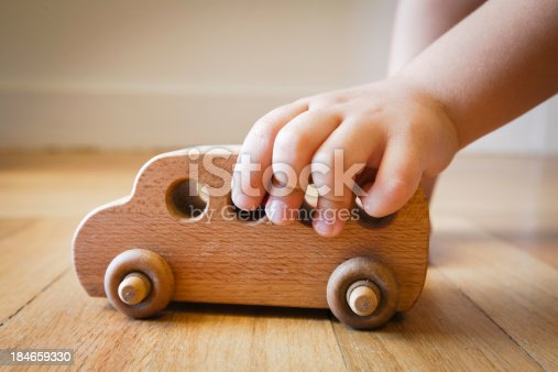 184659330 istock photo Child playing with wooden toy bus on wooden floor 184659330