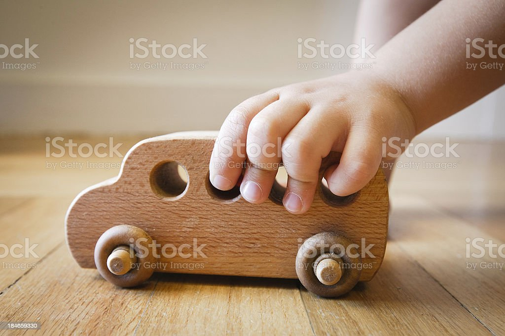 Child playing with wooden toy bus on wooden floor stock photo