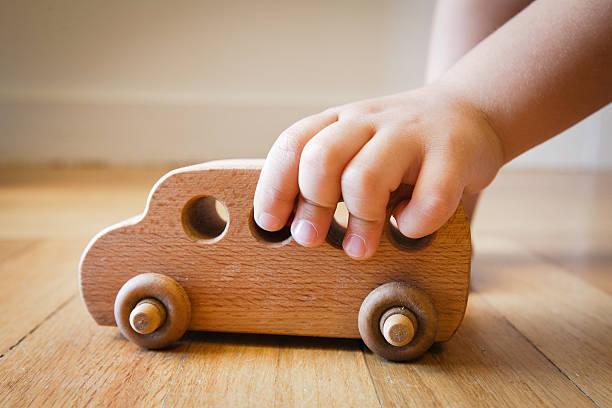 kind spielen mit holz spielzeug bus auf holzfußboden - holzspielwaren stock-fotos und bilder