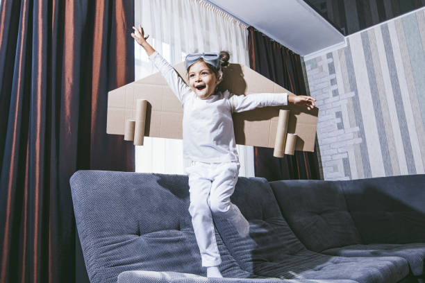 Child plays in the costume of the pilot and wants to fly in the sky stock photo