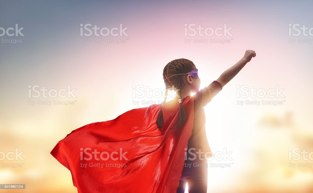 child plays superhero stock photo