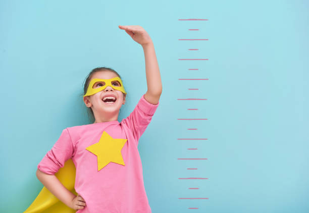 child plays superhero - measuring stock photos and pictures