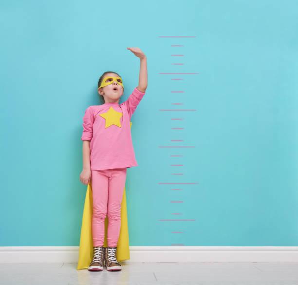 child plays superhero stock photo