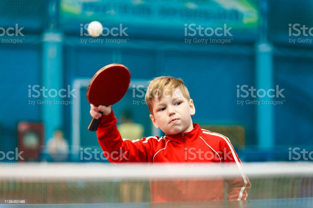 child plays table tennis in the gym, hit the ball with racket
