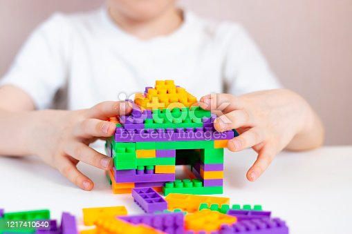544818734 istock photo A child plays with a bright constructor on a white table. Children's creativity in quarantine. Early development of children. House from the designer. 1217410540