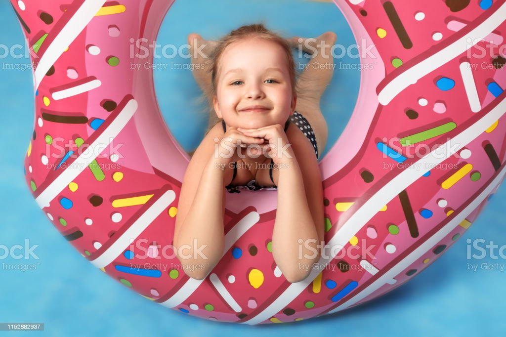 A child plays with a rubber ring in the studio. The little girl is...