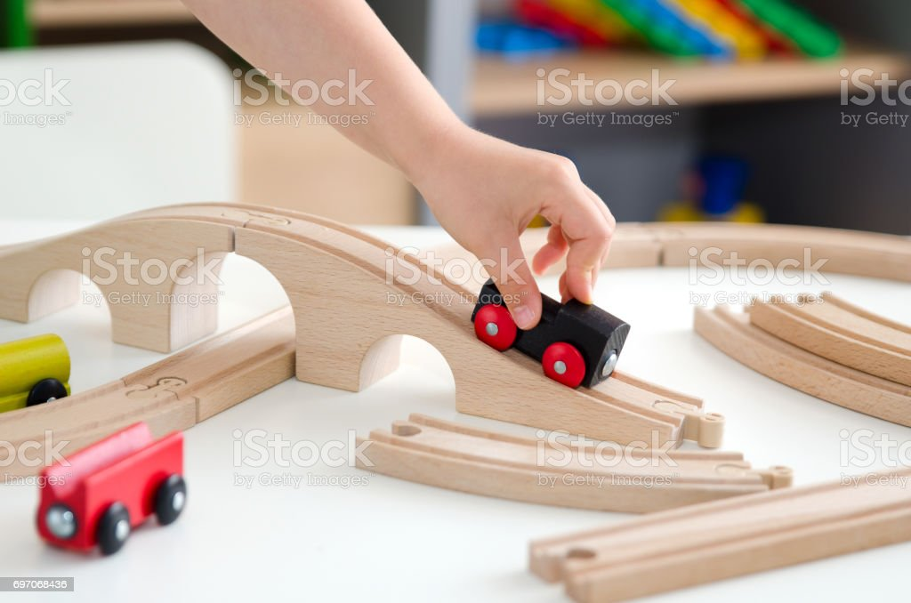 Child plays with a wooden toy train stock photo
