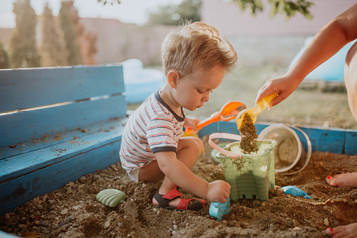 Child plays with his single mother in the sandbox