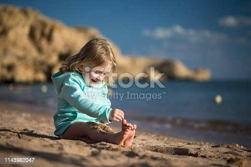 The child sits on the beach and plays with sand. Rest in Egypt. Sharm El Sheikh.