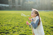Child girl plays with soap bubbles on the green grass.
