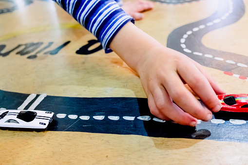 Child plays with two miniature cars in a toy circuit.
