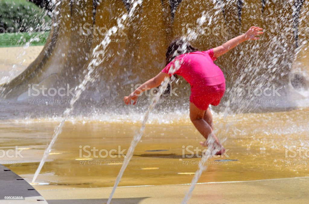 Child plays with water fountain stock photo