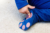 A child indicates the safety non-slip patches on the feet of his onesie-style sleepsuit.