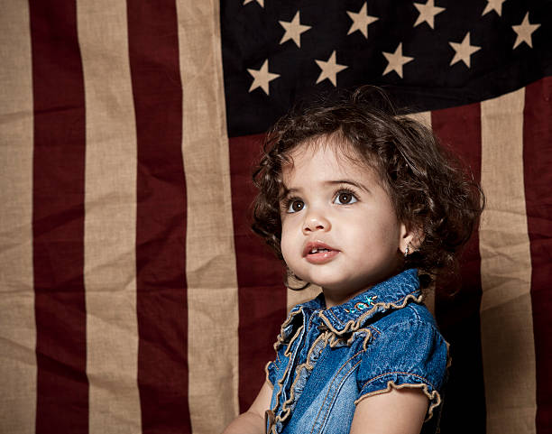 Child posing in front of american flag stock photo