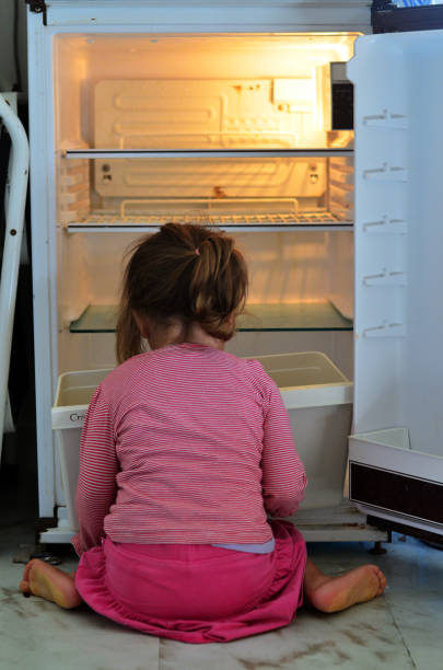 Child Poverty Hungry Poor little girl looks for food in an empty fridge at home. hungry stock pictures, royalty-free photos & images