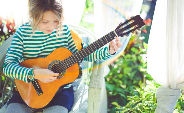 Child practicing the guitar on the front porch stock photo