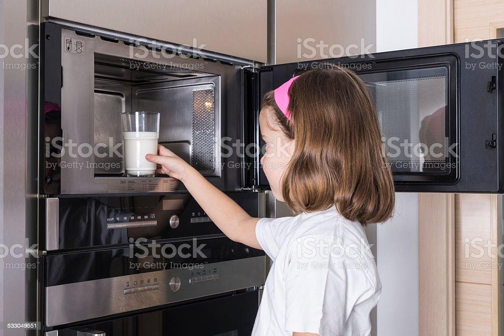 Child preparing a glass of milk stock photo