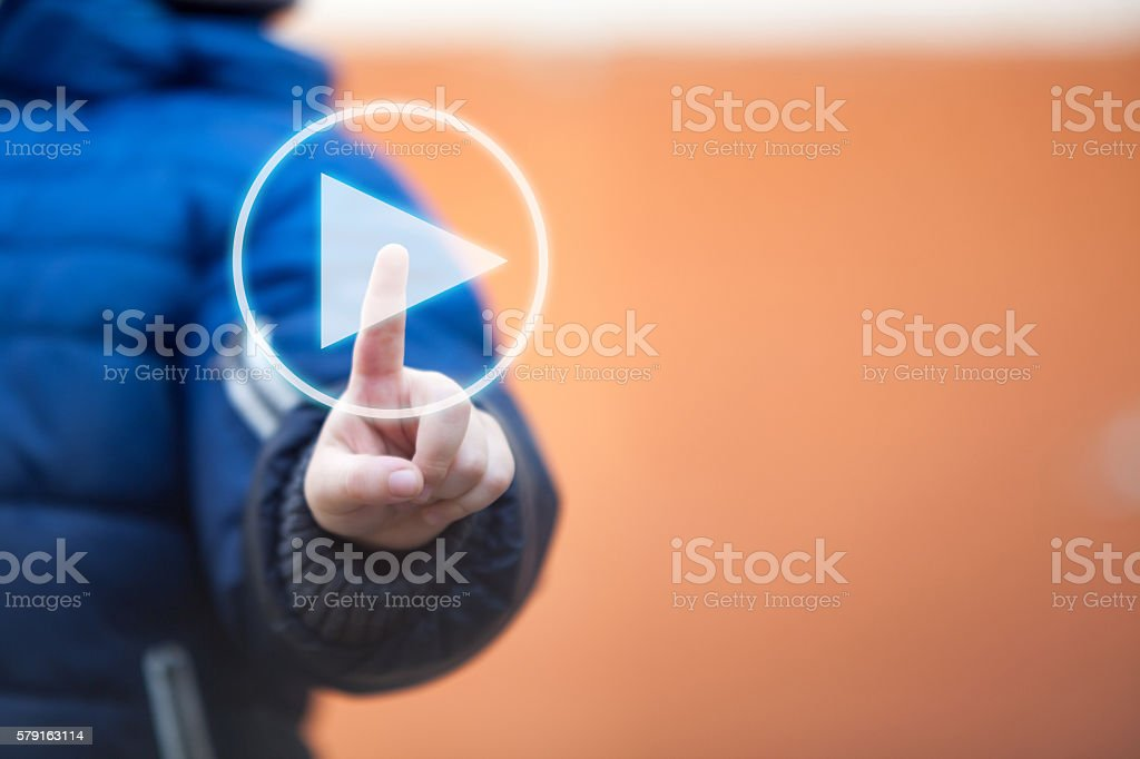 Child pressing play button on touch screen. - foto de stock