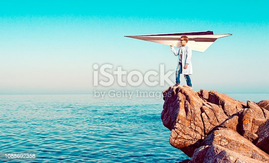 Boy wears a lab coat and stands on a cliff over looking the sea. He holds on to a large paper airplane and he is ready to let it take off. Concept of dreaming big and using imagination to reach your goals.