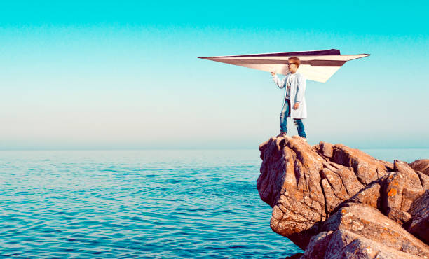 Child prodigy has created a large paper plane and is ready to let it take off Boy wears a lab coat and stands on a cliff over looking the sea. He holds on to a large paper airplane and he is ready to let it take off. Concept of dreaming big and using imagination to reach your goals. child prodigy stock pictures, royalty-free photos & images