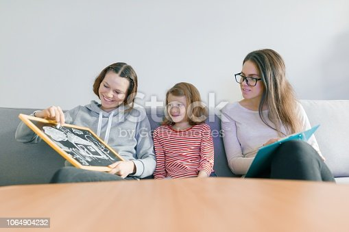 istock Child professional psychologist working with family, two sisters in the office 1064904232