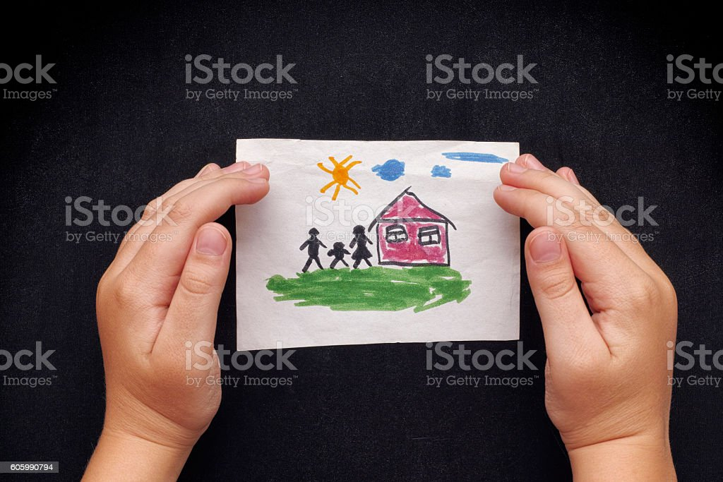 Child protects a drawn house with family stock photo
