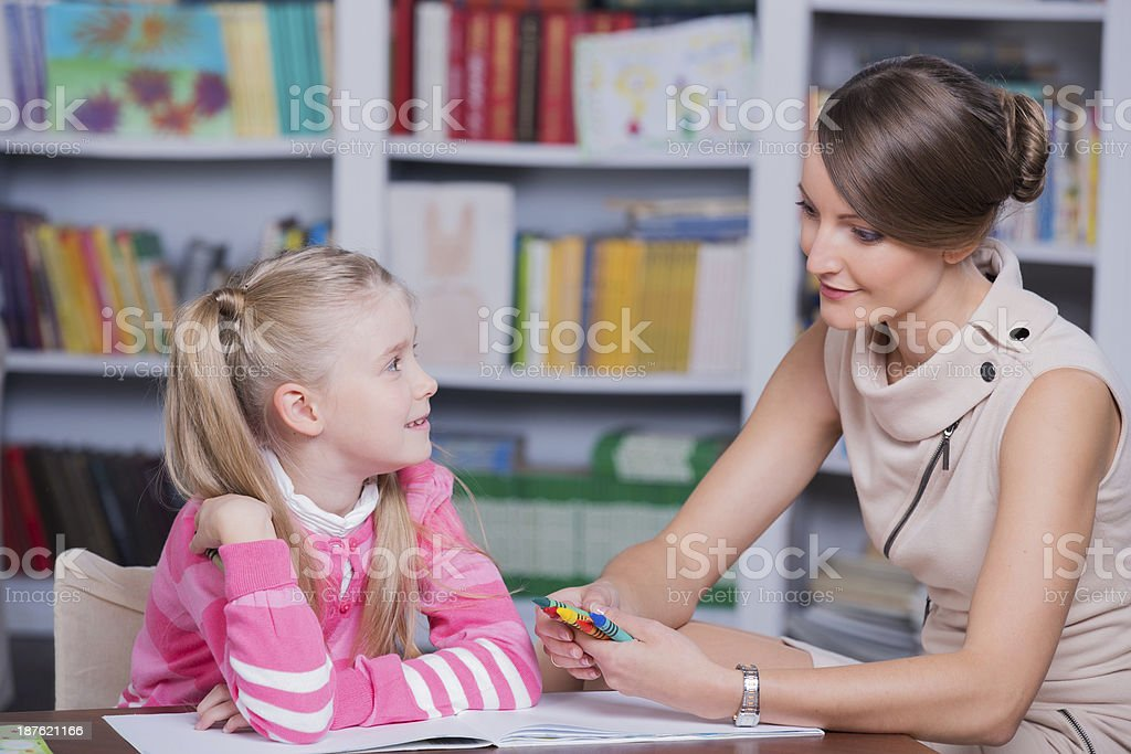 Child psychologist talking to little girl at her office stock photo