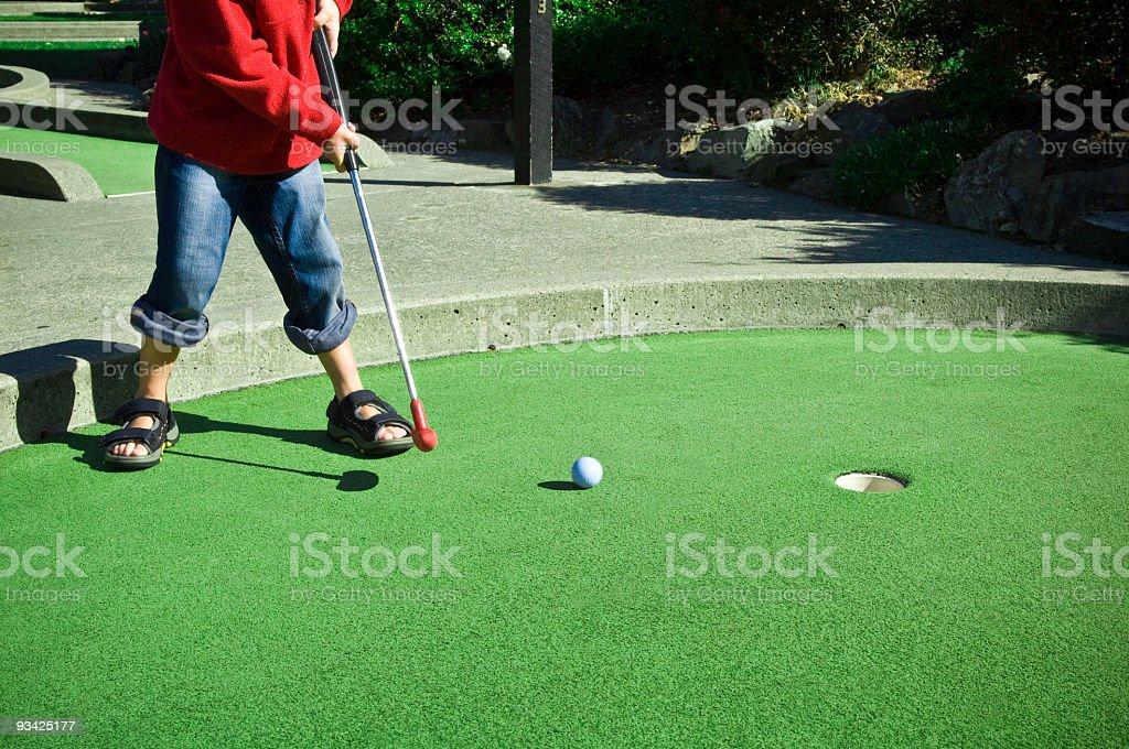 Child putting ball on miniature golf course stock photo