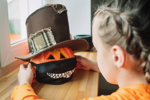 niño poniendo máscara protectora en jack o'lantern para halloween - halloween covid fotografías e imágenes de stock