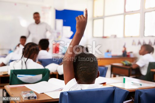 1160928955 istock photo Child raising hand to answer in an elementary school lesson 803138906