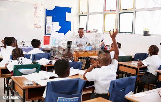 1160928955 istock photo Child raising hand to teacher in an elementary school class 803139852