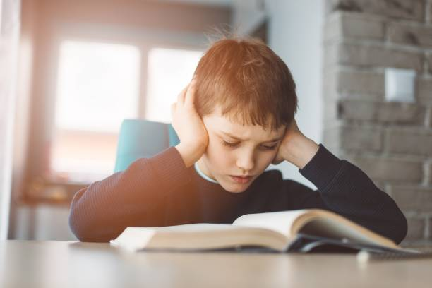 Child reading a book at the desk stock photo