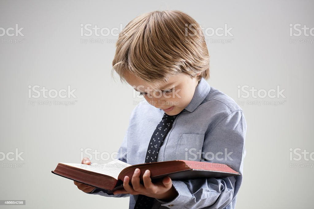 Child reading a book or bible stock photo