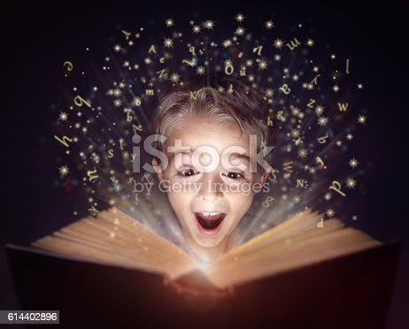 istock Child reading a magic story book 614402896