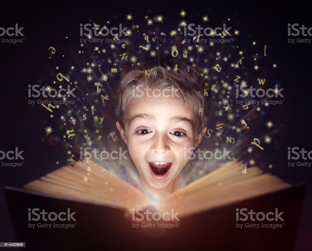 Child reading a magic story book stock photo