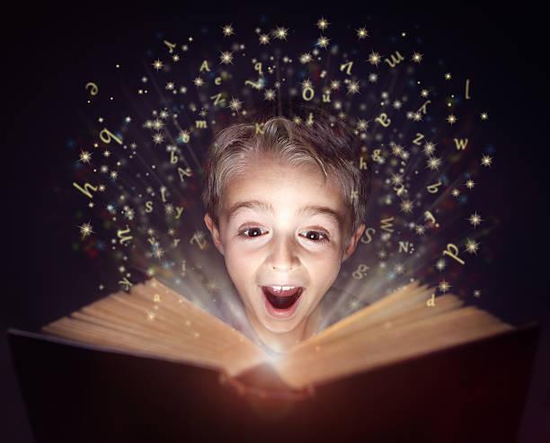 child reading a magic story book - geschichten für kinder stock-fotos und bilder