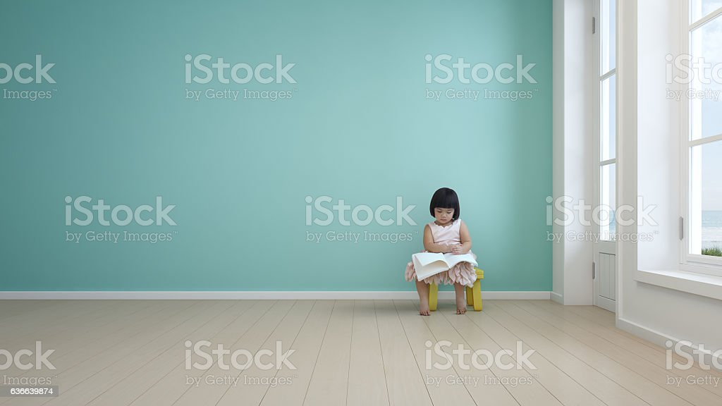 Child reading book in kids room of modern beach house stock photo