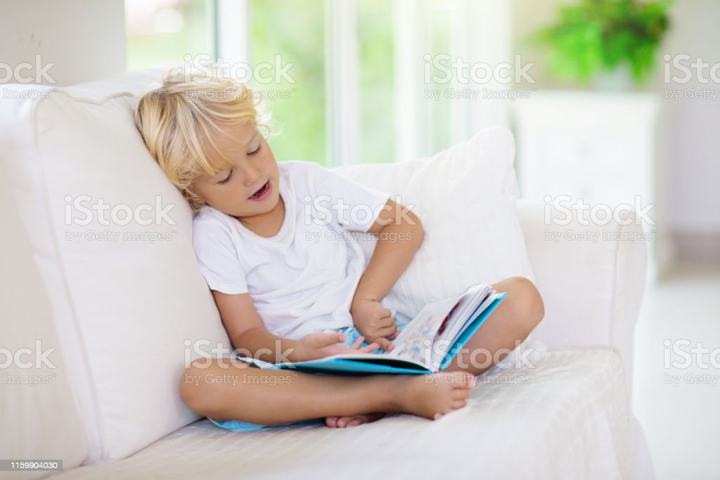 Child reading book. Kids read books. Little boy sitting on white...