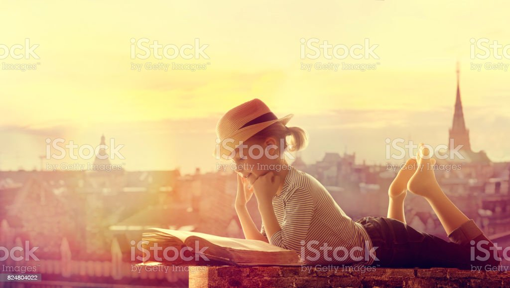 Child Reading Book Outdoor City Roof, Happy Girl Kid Read and Dream Children Books stock photo