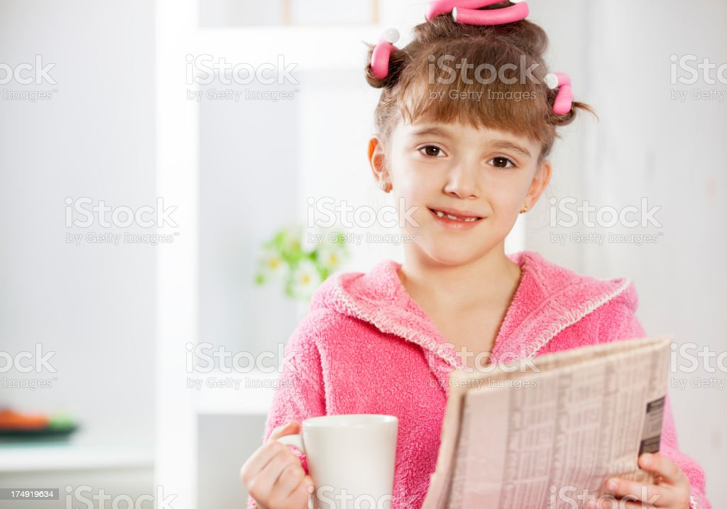 Child reading newspapers and drink tea royalty-free stock photo