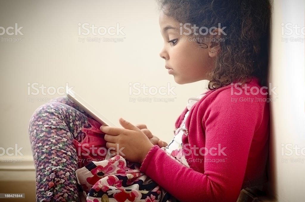 Child (5-6) Reading on Digital Graphic Tablet  At home stock photo