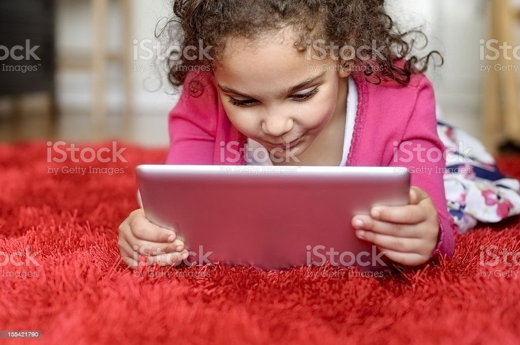 Child (5-6) Reading on Digital Graphic Tablet  At home royalty-free stock photo