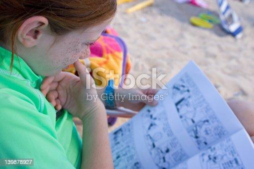 istock Child Reading on the Beach 139878927