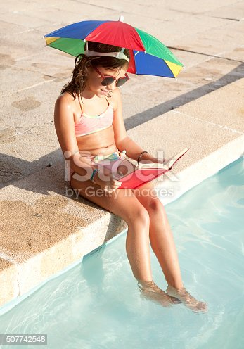 Child reading on the swimming pool