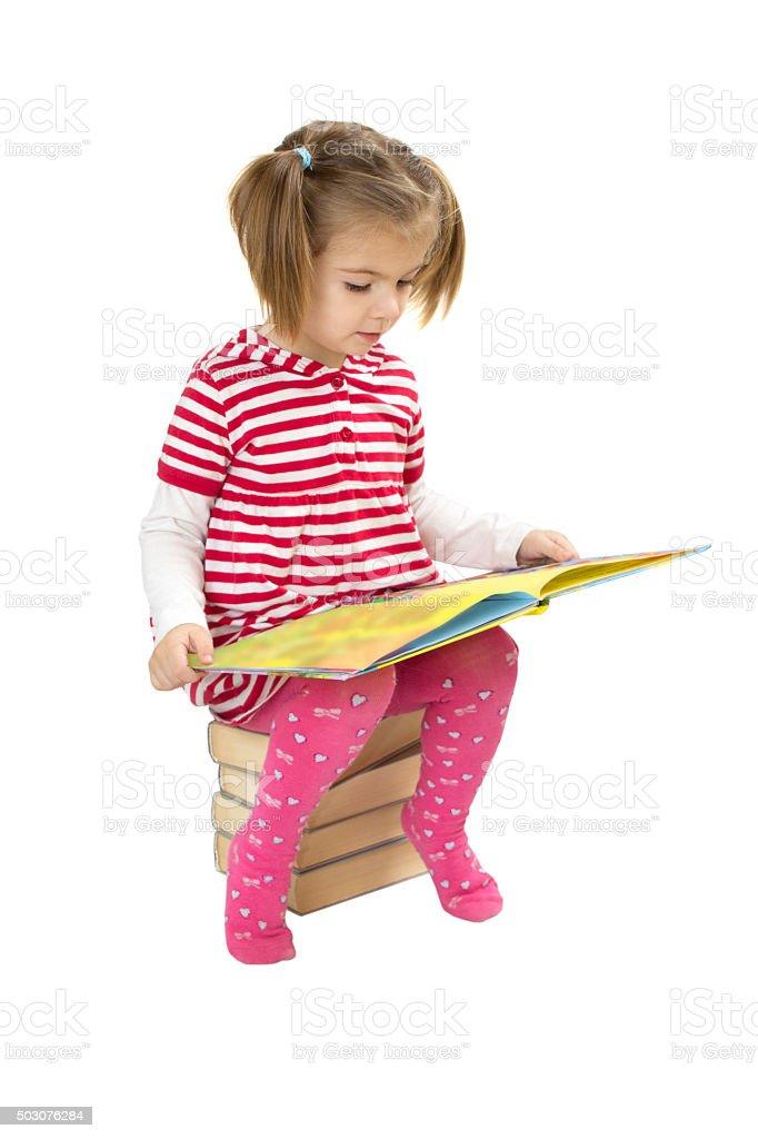 Child reading pile of books stock photo