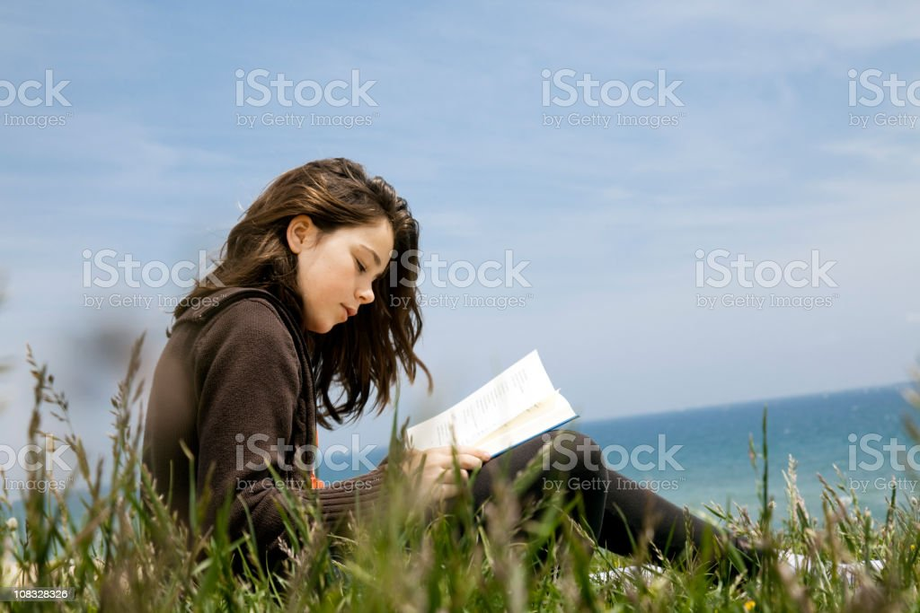 Child reading poetry by the sea stock photo