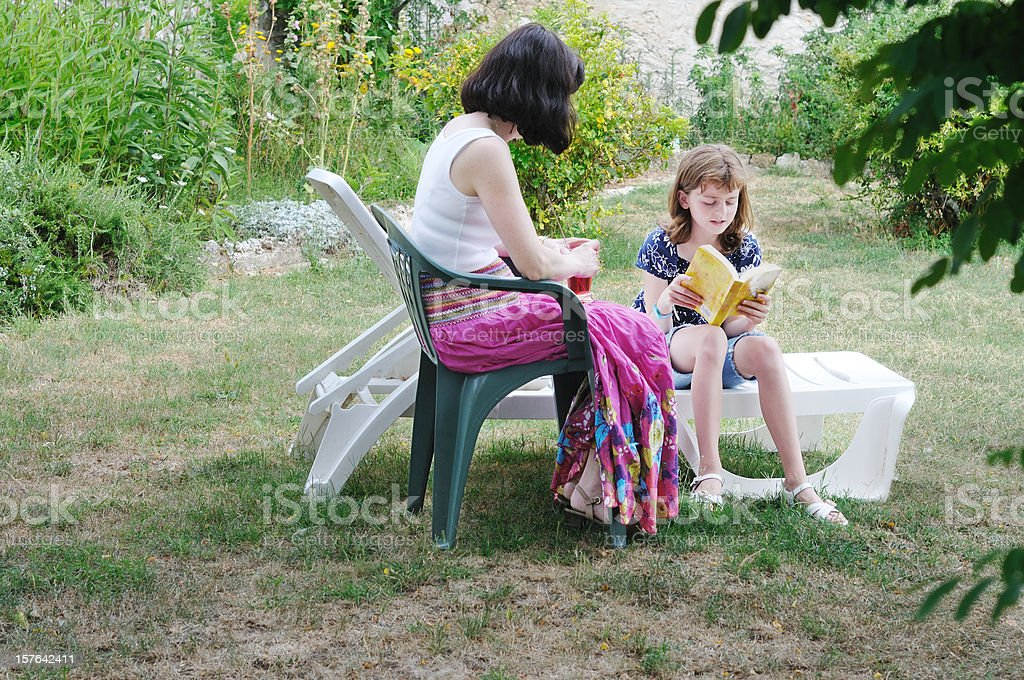 child reading to her mother in the garden stock photo