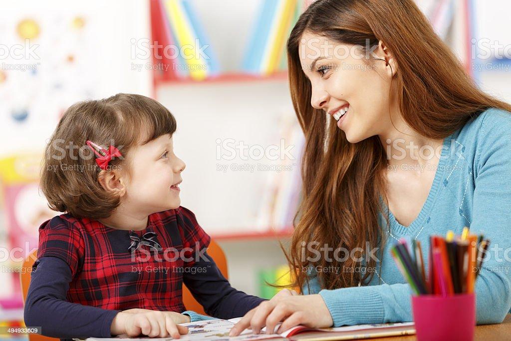 Child reading with a preschool teacher stock photo