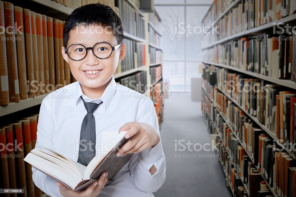 Child reads book in the library aisle royalty-free stock photo